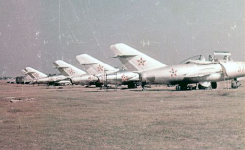 Hungarian MiG-15UTI, MiG-15bis, Yak-18 and Yak-11 trainer aircrafts on the grass airport. The MiG-15 type was used to train young pilots returning from the Soviet Union.